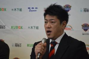 岡田選手の隣で「優勝」と語る佐古賢一ヘッドコーチ
